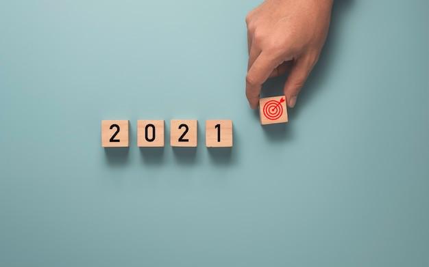 Empresario sosteniendo el objetivo que imprime la pantalla en un bloque de cubo de madera con el año 2021, configurar el concepto de objetivo empresarial.