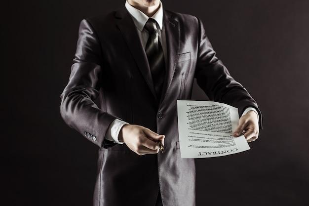 Empresario sosteniendo una pluma y un documento con los términos del contrato