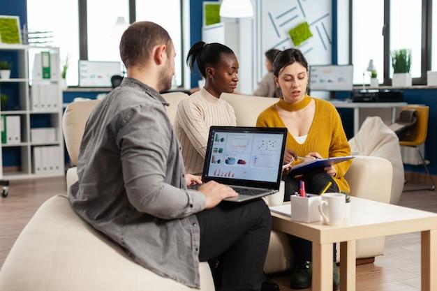 Empresario sosteniendo portátil con ghraphics financieros mientras diversos empleados hablan