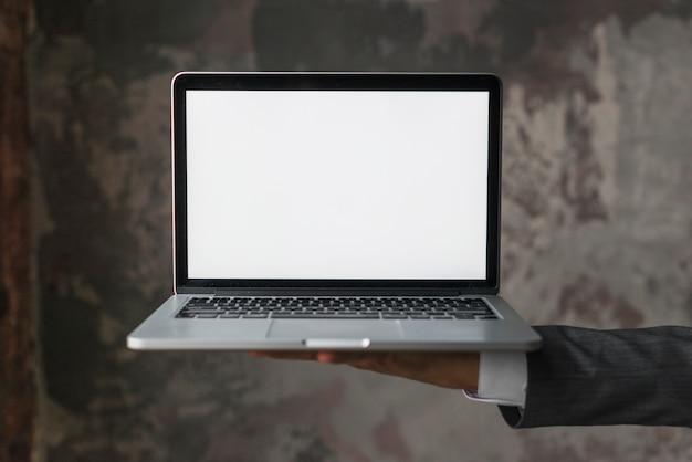 Empresario sosteniendo portátil con pantalla en blanco en blanco