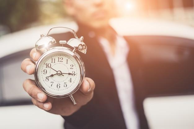 Empresario sosteniendo el reloj retro frente al auto blanco