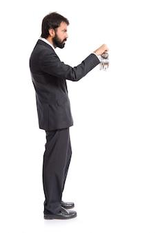 Empresario sosteniendo un reloj sobre fondo blanco