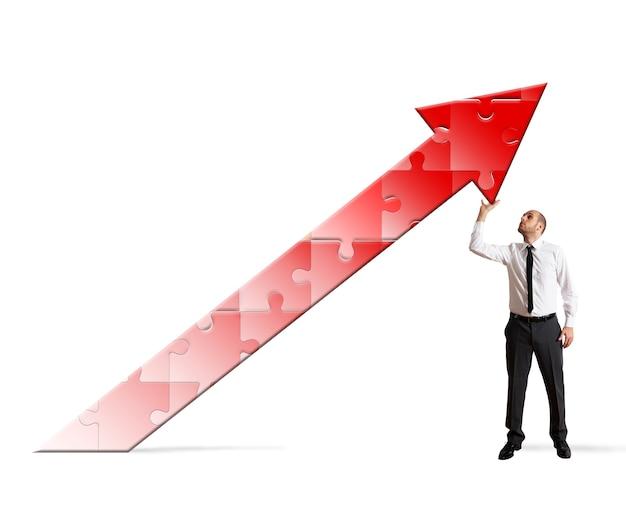 Empresario sosteniendo un rompecabezas con flecha apuntando hacia arriba