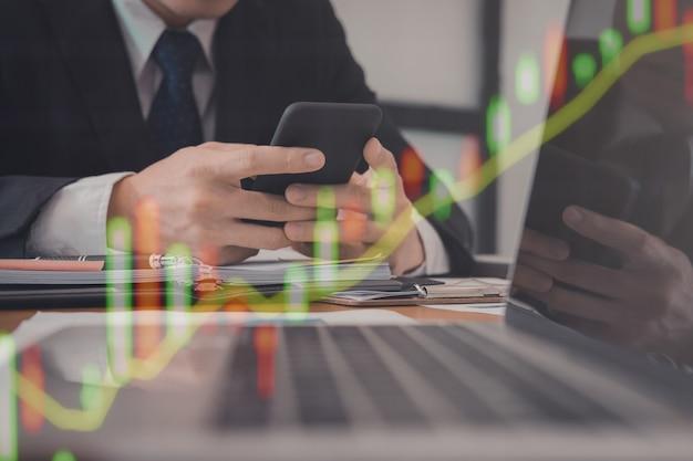 Empresario sosteniendo smartphone y usando la aplicación. hombre mensajes de texto doble exposición con gráfico del mercado de valores
