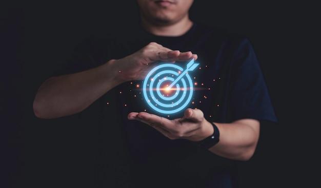 Empresario sosteniendo un tablero de dardos azul virtual con flecha, concepto de objetivo de logro empresarial.