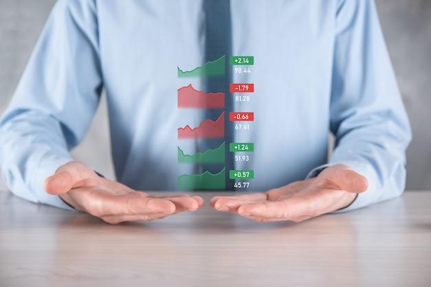 Empresario sosteniendo tableta y análisis del mercado de valores, cambio de divisas y banca, mostrando un holograma virtual creciente de estadísticas, gráficos y tablas, crecimiento empresarial, concepto de planificación y estrategia.