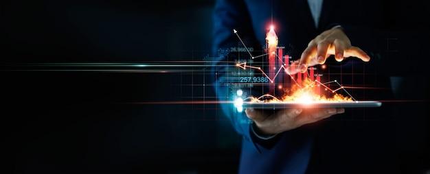 Empresario sosteniendo la tableta y un fuego ardiente que brilla intensamente flecha vertical financiera y bancaria