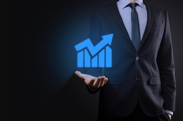 Empresario sosteniendo la tableta y mostrando un creciente holograma virtual de estadísticas, gráficos y tablas con la flecha hacia arriba en la pared oscura. bolsa de valores. concepto de estrategia, planificación y crecimiento empresarial.
