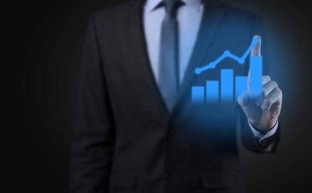Empresario sosteniendo la tableta y mostrando un creciente holograma virtual de estadísticas, gráficos y tablas con la flecha hacia arriba sobre fondo oscuro. bolsa de valores. concepto de estrategia, planificación y crecimiento empresarial.