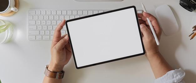 Empresario sosteniendo la tableta de la pantalla en blanco sobre el teclado de la computadora y suministros en el escritorio de oficina blanco