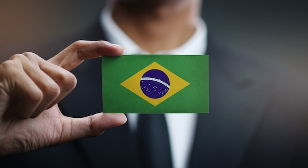 Empresario sosteniendo la tarjeta de la bandera de brasil