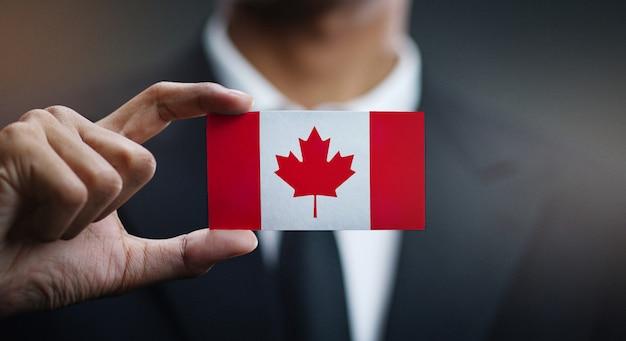 Empresario sosteniendo la tarjeta de bandera de canadá