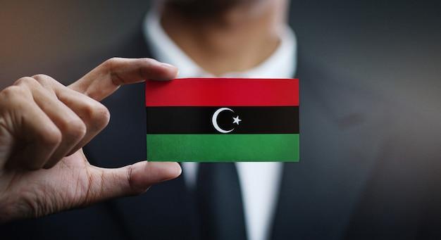 Empresario sosteniendo la tarjeta de la bandera de libia