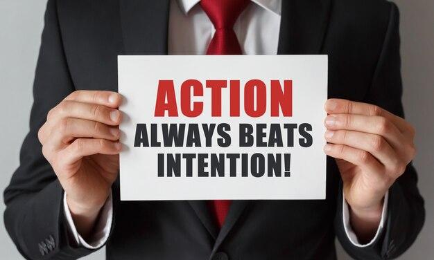 Empresario sosteniendo una tarjeta con texto la acción siempre es mejor que la intención