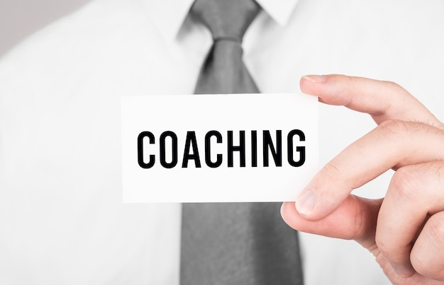 Empresario sosteniendo una tarjeta con texto coaching, concepto de negocio