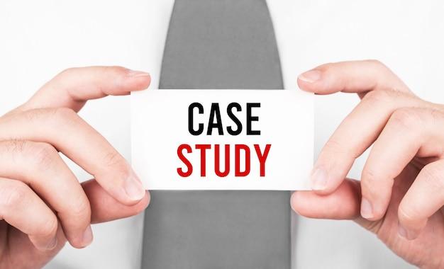 Empresario sosteniendo una tarjeta con texto estudio de caso, concepto de negocio
