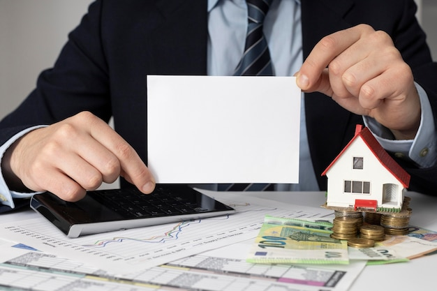 Empresario sosteniendo una tarjeta vacía junto a una casa en miniatura