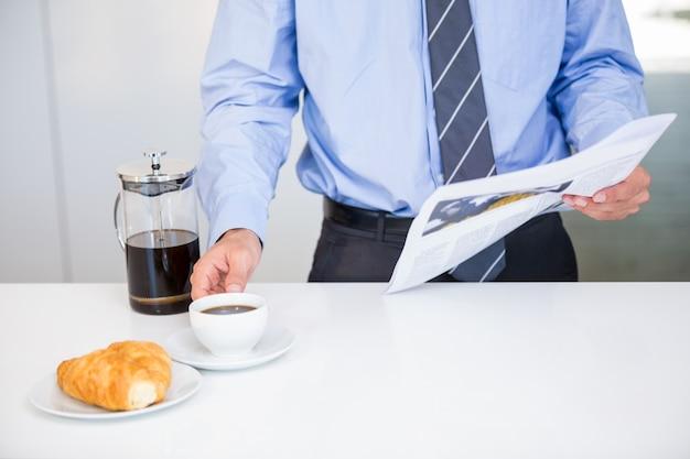 Empresario sosteniendo la taza de café y periódico por mesa