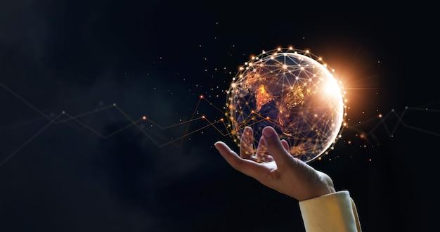 Empresario sosteniendo la tierra de la noche y los intercambios de datos de redes globales comunicación global