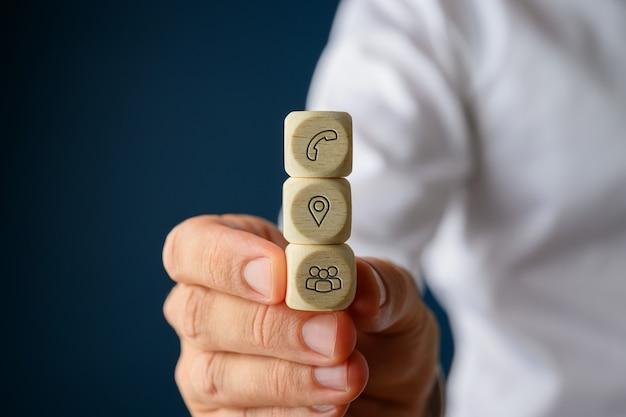 Empresario sosteniendo tres dados de madera apilados con iconos de contacto e información en ellos.