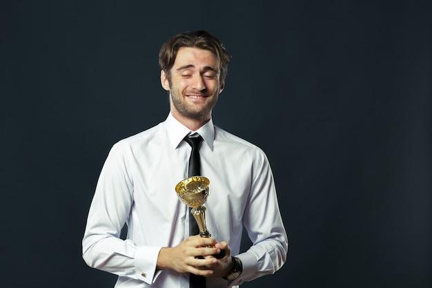 Empresario sosteniendo el trofeo de la copa de oro