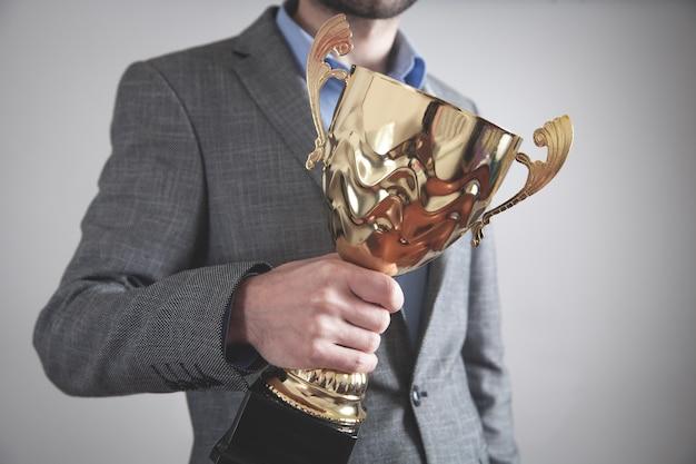 Empresario sosteniendo trofeo de oro.