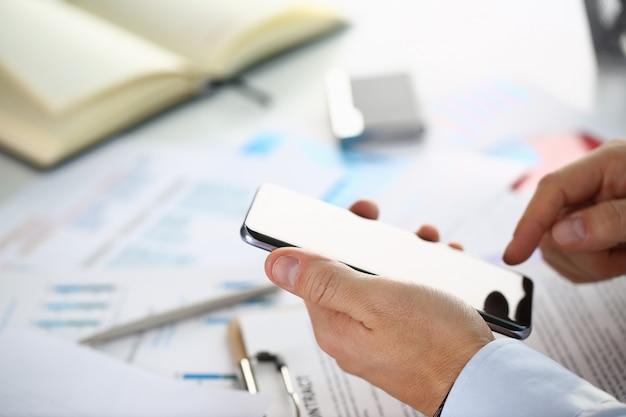 Un empresario sostiene un nuevo teléfono inteligente