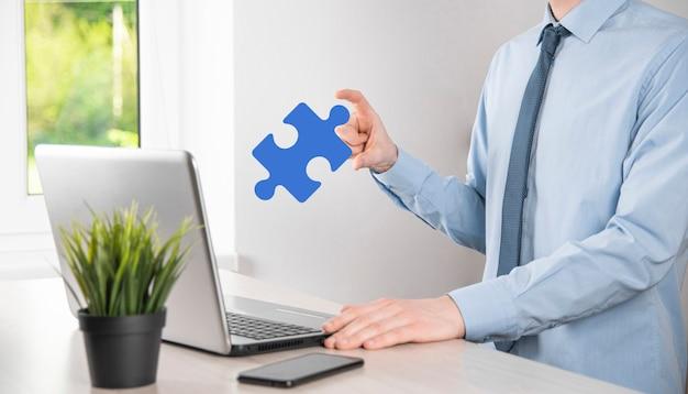 El empresario sostiene una pieza de rompecabezas en sus manos.el concepto de cooperación, trabajo en equipo, ayuda