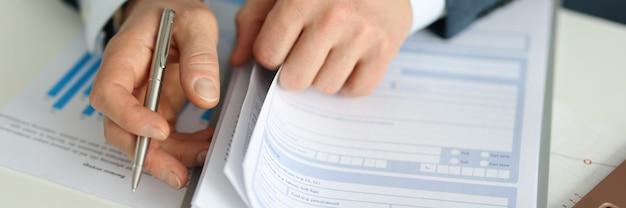 El empresario sostiene la pluma y estira el formulario de solicitud para firmar el concepto de documentos de seguro