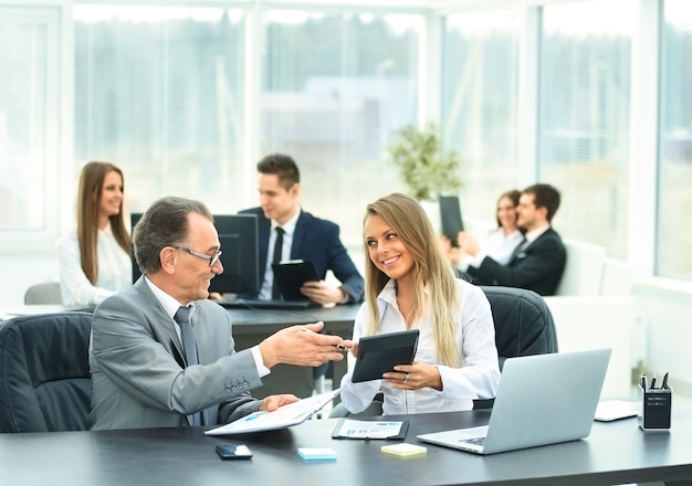 El empresario y su asistente discuten el plan de trabajo de la empresa.