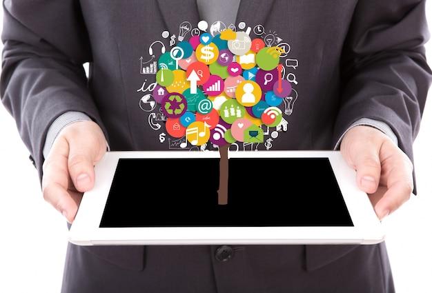 Empresario sujetando una tableta con iconos de colores