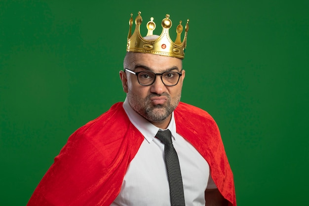 Empresario de superhéroe en capa roja y gafas con corona mirando al frente de pie auto-satisfecho sobre la pared verde