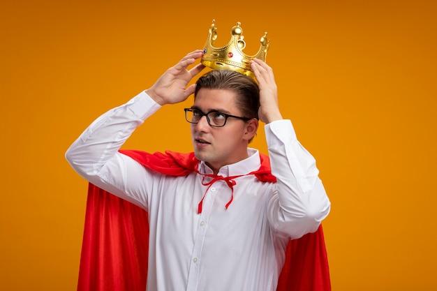 Empresario de superhéroe en capa roja y gafas con corona tocándola con cara seria de pie sobre la pared naranja