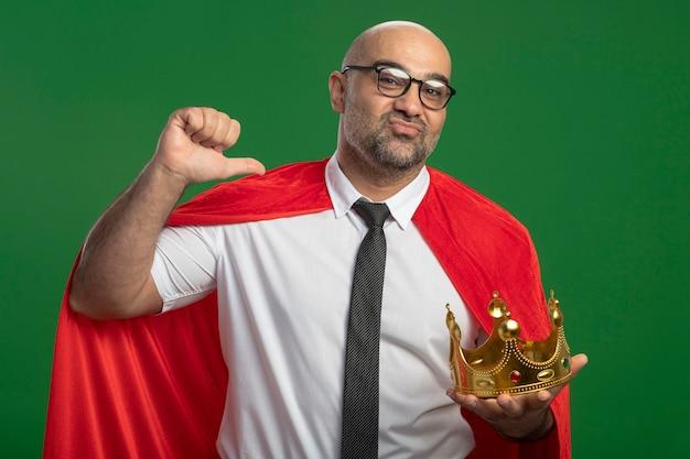 Empresario de superhéroe en capa roja y gafas sosteniendo corona apuntando a sí mismo sonriendo confiado de pie sobre la pared verde