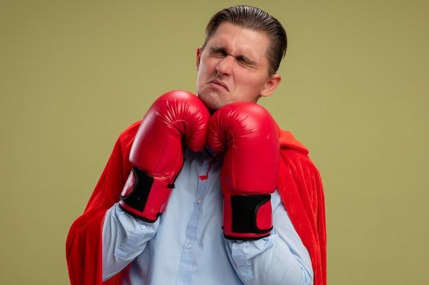 Empresario de superhéroe en capa roja y guantes de boxeo con ojos cerrados con expresión triste en la cara de pie sobre fondo claro