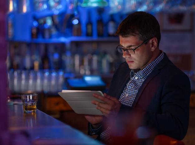 Empresario con tablet pc y whisky en la barra de bar