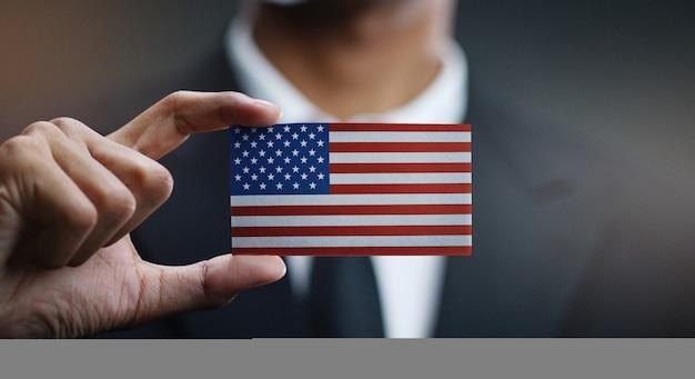 Empresario con tarjeta de bandera de los estados unidos de américa