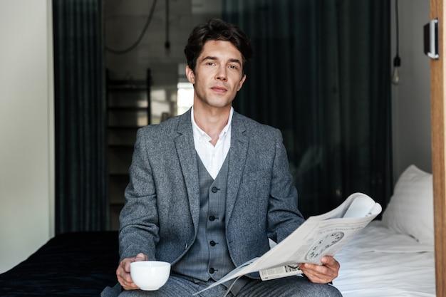 Empresario con taza de café leyendo periódico