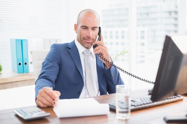 Empresario en el teléfono y escribiendo notas