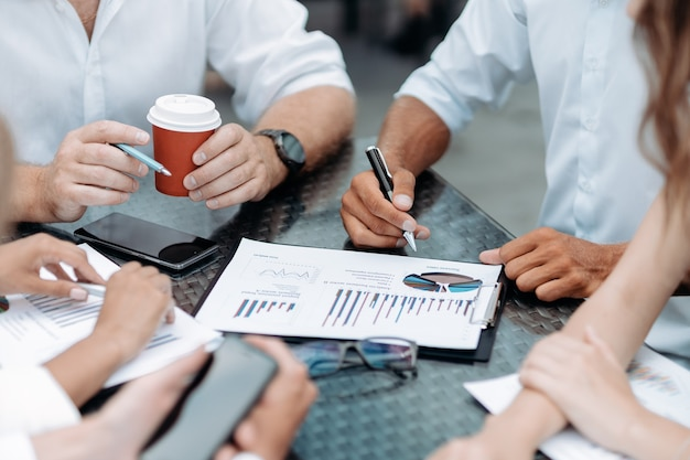 Empresario con un teléfono inteligente durante una reunión de oficina