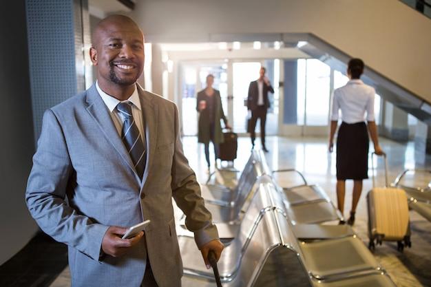 Empresario con teléfono y maleta con ruedas de pie en la terminal del aeropuerto