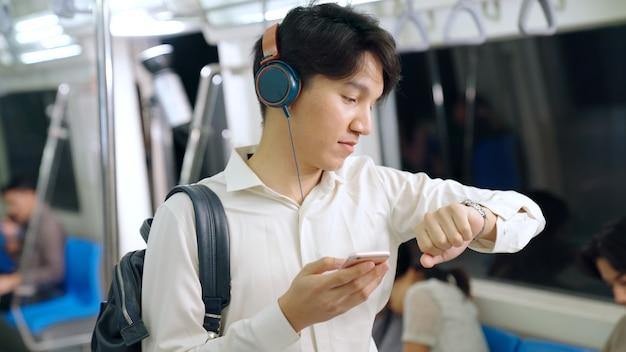 Empresario mediante teléfono móvil en tren público. concepto de desplazamiento del estilo de vida urbano de la ciudad.