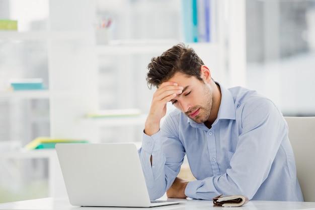 Empresario tenso sentado en la mesa con laptop