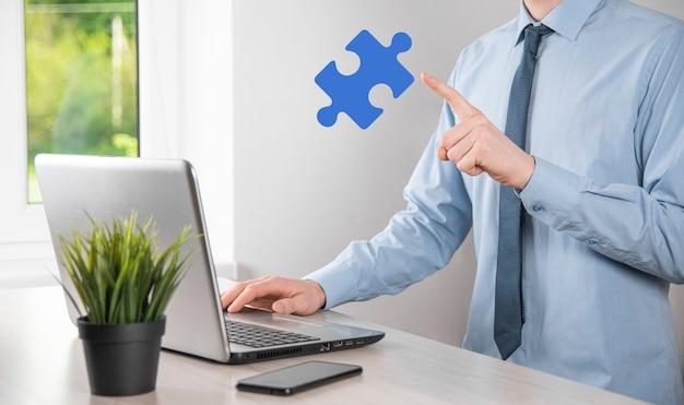 El empresario tiene una pieza de rompecabezas en sus manos. el concepto de cooperación, trabajo en equipo, ayuda y apoyo en los negocios.