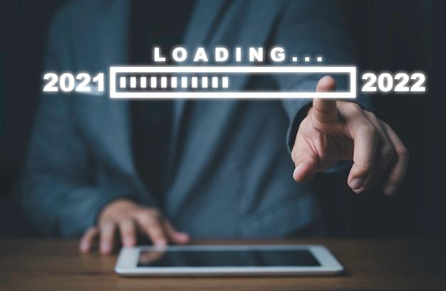 Empresario tocando la descarga virtual de 2021 a 2022 progresiva, feliz navidad y feliz año nuevo, preparación y concepto de cuenta regresiva.