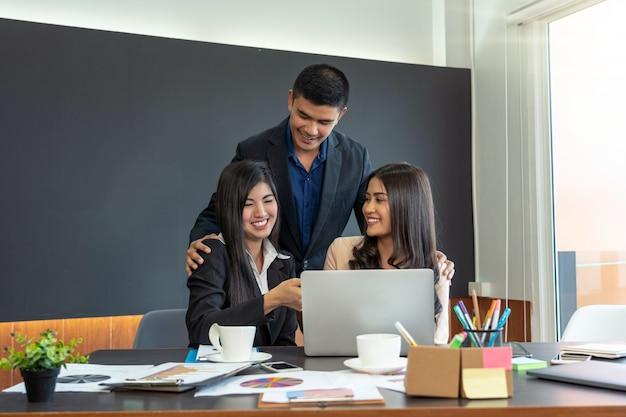 Empresario tocando dos empresaria asiática con traje formal en oficina moderna cuando workin