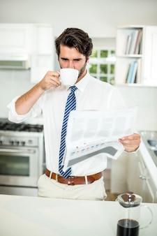 Empresario tomando café mientras leía el periódico en la mesa