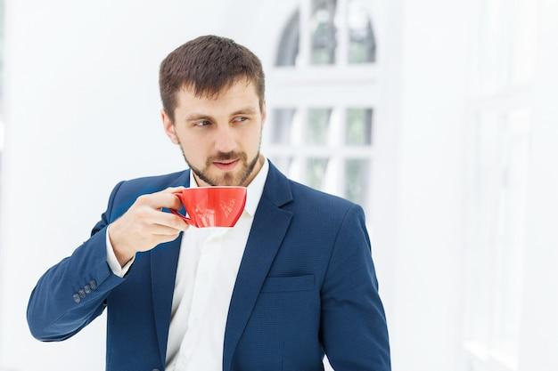 Empresario tomando café, él está sosteniendo una taza