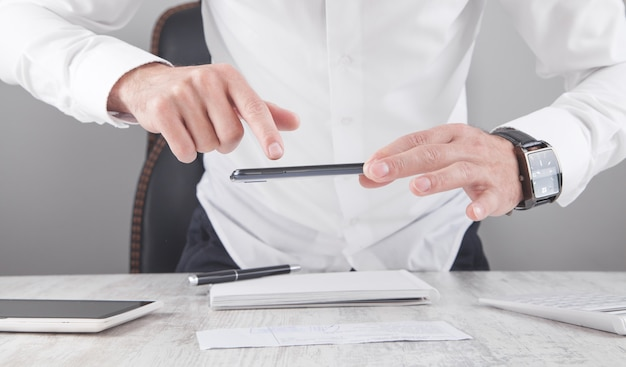 Empresario tomando fotos de documentos con smartphone