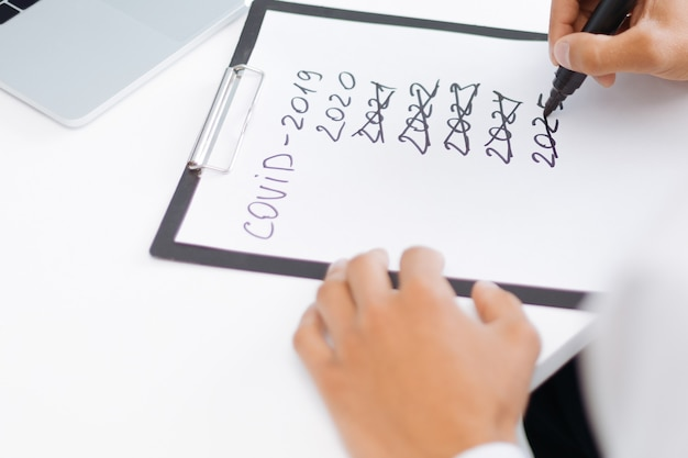Empresario tomando notas sobre las consecuencias de la cuarentena
